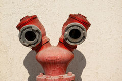 Red fire hydrant by a wall Royalty Free Stock Photography