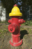 A red fire hydrant with a yellow top is seen roadside in New England Royalty Free Stock Photography