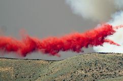 Red Fire Retardant Suspended in Midair After Being Dropped on a Raging Wildfire Royalty Free Stock Photos