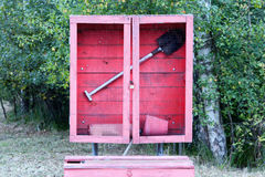 Red fire shield with a shovel in a forest Stock Images