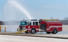 Red Fire Truck in action. A fire truck is flushing the water canon on a parking lot royalty free stock photo