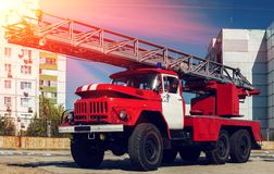 Red fire truck with a ladder at sunset. Stock Photography