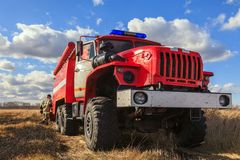 Red fire truck Ural and firefighters are standing on the field w royalty free stock photos