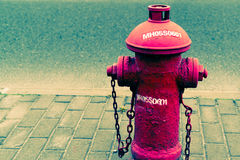 The red fire water hydrant beside the road - hipster filter and nois. Red fire water hydrant beside the road - hipster filter and noise grain style Stock Photo