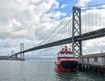 Fireboat at dock next to Oakland Bay Bridge in San Francisco California stock photography