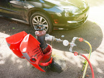 Red firefighter water hydrant with water meter used by the city Stock Image