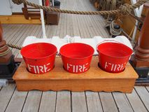 Red Firefighting Buckets on Sailing Ship. Bright red buckets for firefighting on the wooden deck of an historical tall sailing ship, Sydney, Australia stock photos