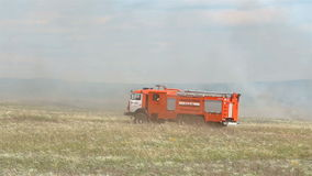 Red firemachine moving accros field. Fire engine across battlefield stock video