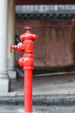 Red fireplug standing on footpath Royalty Free Stock Photography