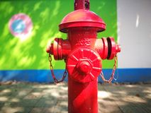 Red fireplug standing before the green wall Royalty Free Stock Photography