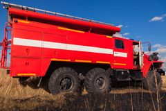 Red firetruck car Ural rides through the autumn field with yellow and faded grass against the blue sky and clouds. The concept royalty free stock photo