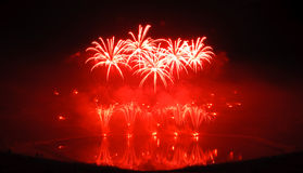 Red Fireworks. Multiple fireworks in a composition in shades of red, reflecting in water. Photograph taken during a fireworks festival; the silhouette of the stock photography