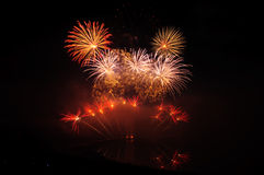 Red Fireworks. Multiple fireworks in a composition in shades of red, reflecting in water royalty free stock photos