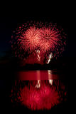 Red Fireworks Reflected on Water. Red fireworks reflected on the water of the Glenmore Reservoir Royalty Free Stock Image