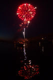 Red Fireworks and Reflection in River. A red fireworks explodes over a river during a holiday celebration stock photo