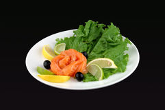 Red fish with. A lemon and salad on a black background Royalty Free Stock Photo