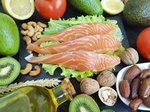 Red fish, avocado nuts on black wooden, healthy food. Red fish, avocado nuts on black wooden butter healthy foodn Stock Photos