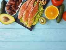 Red fish omega 3 , fresh avocado dinner nuts assortment on blue wooden, composition healthy food. Red fish, avocado nuts on blue wooden healthy food green Stock Photo