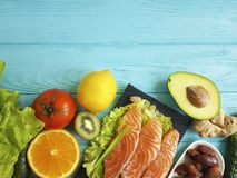 Red fish omega 3 , fresh avocado nuts assortment on blue wooden, composition healthy food. Red fish, avocado nuts on blue wooden healthy food green composition royalty free stock photo