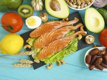Red fish, avocado nuts  dinner  cucumber   wooden, healthy foodred fish, avocado. Red fish, avocado nuts  dinner  cucumber   wooden Royalty Free Stock Photos