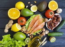 Free Red Fish, Avocado Nuts Selection Dinner Natural Cucumber On Black Wooden, Healthy Food Stock Photography - 111736392