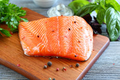 Red fish fillet with greens on a cutting board Stock Image