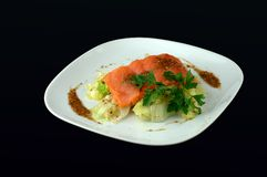 Red fish with a garnish. Red fish with salad on a plate on a black background stock images