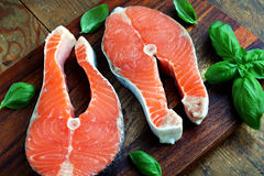 Red fish pieces. Two pieces of red salmon fillets placed on the wooden cutting board Royalty Free Stock Photography