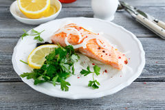 Red fish on a plate with lemon and parsley Royalty Free Stock Images