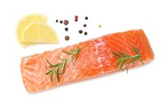 Red fish. Raw salmon fillet with rosemary and lemon isolate on white background. Top view stock image