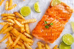Red fish salmon steak fillet with French curly fries. Delicious red fish salmon steak fillet with French curly fries on a white parchment paper with sliced lime Royalty Free Stock Photo