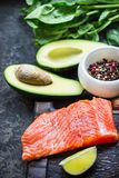 Red fish with spices, greens and avocado on grey stone background. Selective focus. Top view Stock Photo