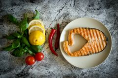 Red fish steak on a plate. Pieces of lemon, hot peppers, ripe tomatoes on a beautiful background. royalty free stock image