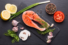 Red fish steak with spices and vegetables on a slate table.  Stock Photo