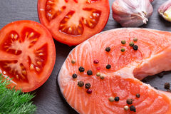 Red fish steak with tomatoes on a slate table.  Royalty Free Stock Images