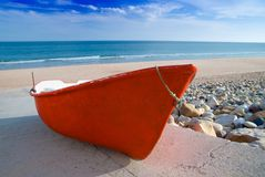 Red Fishing Boat. Small old red fishing boat on the beach royalty free stock image
