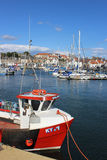 Red fishing boat in Anstruther harbour, Scotland. Small red inshore fishing boat moored in Anstruther harbour in Fife, Scotland with yachts and other small boats stock photo