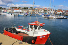 Red fishing boat in Anstruther harbour, Scotland. Small red inshore fishing boat moored in Anstruther harbour in Fife, Scotland with yachts and other small boats royalty free stock photos