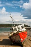 Red fishing boat beached at low tide Royalty Free Stock Images