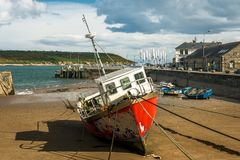 Red fishing boat beached at low tide Royalty Free Stock Photography
