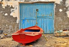 Red fishing boat. And a blue door in Santorini, Greece stock photo