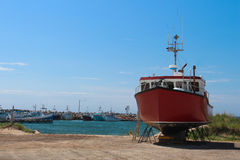 Red fishing boat in dry dock. In Magdalen Island with port and other boats in the background uner a blue sky Royalty Free Stock Images
