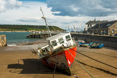 Red fishing boat moored at low tide Stock Image