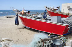The red fishing boat on the ocean shore Stock Photo