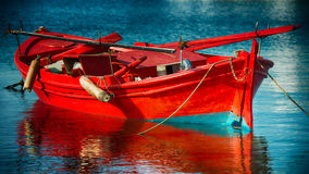 Red fishing boat. Red boat reflected on sea water Stock Image