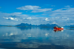 Red fishing boat. Sailing on water with mountains in distance near Svolvaer in Norway stock photo