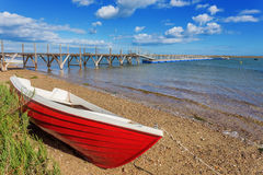 Red fishing boat on the shore. The sea stock photos