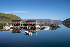 Red Fishing Cabins. A small fishing boat harbor in Norway with red cabins stock image