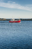Red fishing cutter on blue water. Lofoten Island Royalty Free Stock Photo