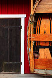 Red fishing hut with black door and wooden boat Royalty Free Stock Images